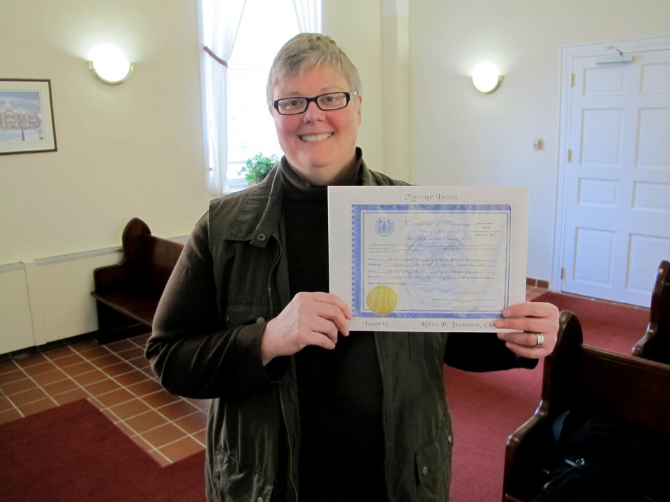 Kim Hinken, of Edgewater, Md., holds the marriage license she obtained Thursday in Anne Arundel County Circuit in Annapolis, Md., to marry her same-sex partner, Adrianne Eathorne. It was the first day same-sex couples could get a Maryland marriage license, which will be effective Jan. 1, when the law takes effect. Hinken, pictured in the courthouse chapel, was the person to get a same-sex marriage license in Anne Arundel County.    (AP Photo/Brian Witte)