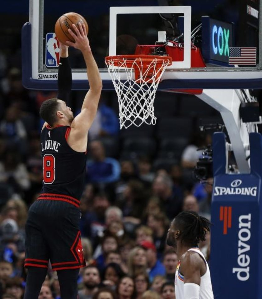 Photo -  Chicago's Zach LaVine dunks the ball next to Oklahoma City's Nerlens Noel during the first half of Monday night's game at Chesapeake Energy Arena. LaVine finished with a game-high 39 points in the Bulls' loss. [Nate Billings/The Oklahoman]