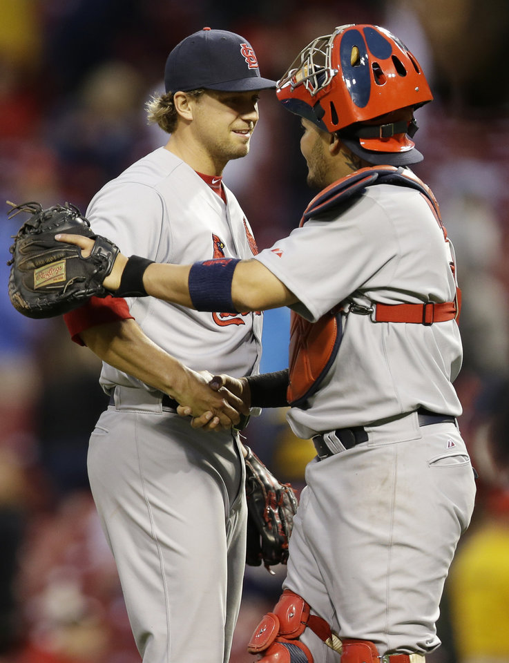 Photo - St. Louis Cardinals relief pitcher Trevor Rosenthal, left, is congratulated by catcher Yadier Molina after they defeated the Cincinnati Reds 7-6 in a baseball game on Thursday, April 3, 2014, in Cincinnati. Rosenthal recorded his second save of the season. (AP Photo/Al Behrman)