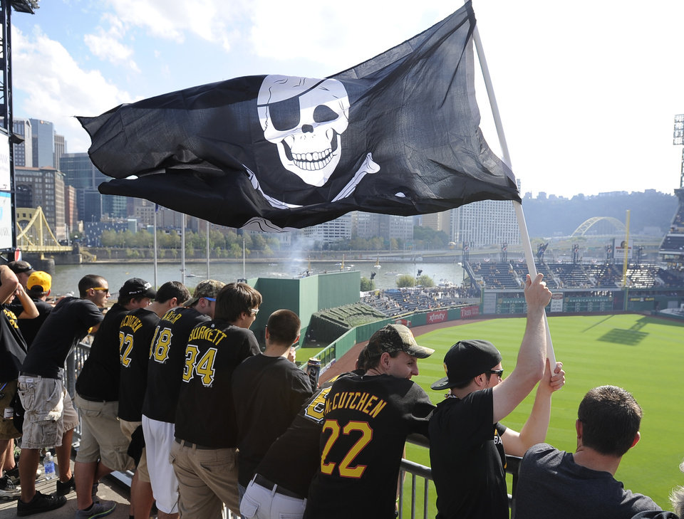 Photo - FILE - In this Oct. 6, 2013, file photo, Pittsburgh Pirates fans wave a Jolly Roger flag as they stand in the left field rotunda before Game 3 of a National League division baseball series between the Pirates and St. Louis Cardinals in Pittsburgh. The Pirates announced on Wednesday, Jan. 8, 2014, the franchise will make the gold