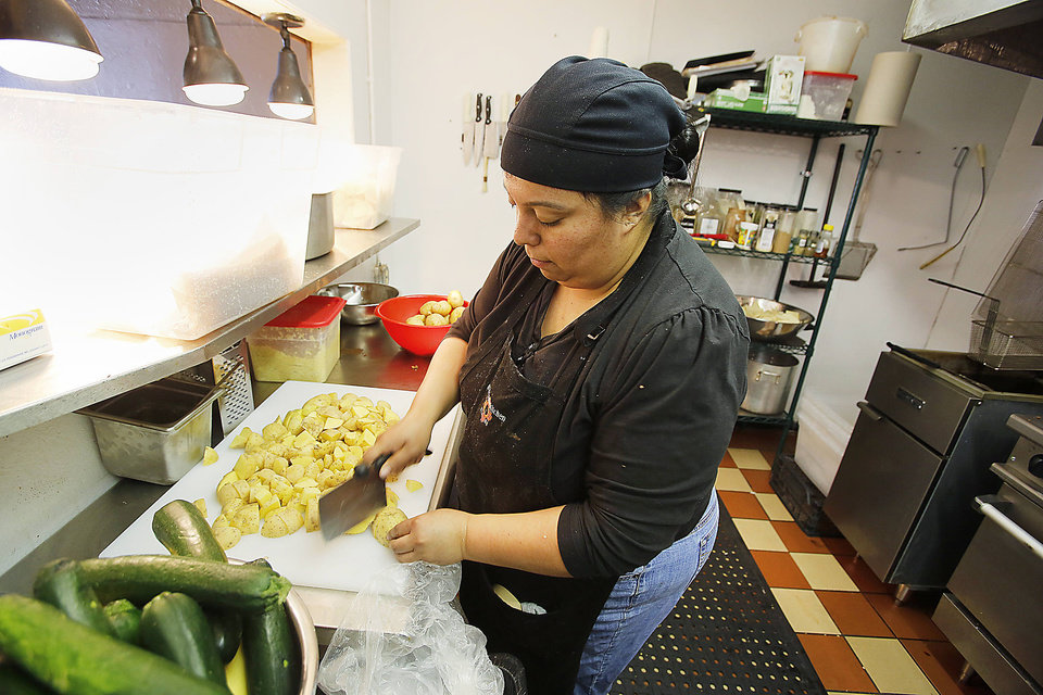 Photo - Maria Cano chops potatoes at the Green Chili Kitchen in Yukon, Friday  January  11, 2013. Photo By Steve Gooch, The Oklahoman