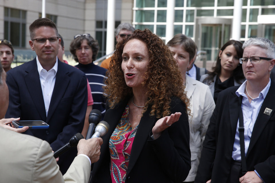 Photo - Attorney Mari Newman, center, talks with members of the media, as she stands with her plaintiffs and their supporters following a court hearing on sam sex marriage at the Federal District Court, in Denver, Tuesday, July 22, 2014. Gay couples seeking to strike Colorado's same-sex marriage ban urged a federal judge Tuesday to overturn the law immediately and reject the state's request to stay a ruling until the U.S. Supreme Court decides the matter. (AP Photo/Brennan Linsley)