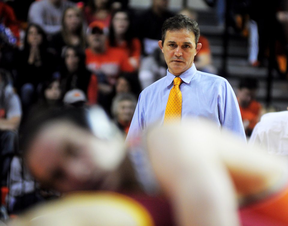 Photo - Oklahoma State wrestling coach John Smith watches 174-pound wrestler Chris Perry takes down Iowa State's Tanner Weatherman at a wrestling dual between Oklahoma State and Iowa State at Gallagher Iba Arena in Stillwater on January 24, 2014. Photo by KT King/For the Oklahoman