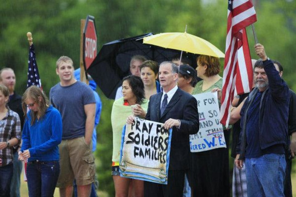 Photo - Supporters holds a signs, in the rain, along I-35 during the funeral for 2nd Lt Jered Ewy, 33, of Edmond, at Henderson Hills Baptist Church.  David McDaniel - THE OKLAHOMAN
