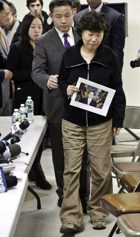 New York City Comptroller John Liu, center, escorts Serim Han, as she holds a picture of her husband Ki-Suck Han, and her daughter Ashley Han, 20, second from left, to a news conference on Wednesday, Dec. 5, 2012 in New York. Naeem Davis, 30, was taken into custody for questioning Tuesday after security video showed a man fitting the suspect\'s description working with street vendors near Rockefeller Center. Police said Davis made statements implicating himself in Ki-Suck Han\'s death. Davis was arrested on a second-degree murder charge. Witnesses told investigators they saw a man talking to himself Monday afternoon before he approached the 58-year-old Han of Queens at the Times Square station, got into an altercation with him and pushed him into the train\'s path. (AP Photo/Bebeto Matthews)