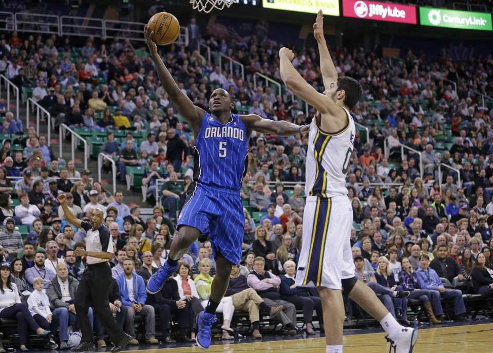 Photo - Orlando Magic's Victor Oladipo (5) goes to the basket as Utah Jazz's Enes Kanter (0), of Turkey, defends in the second quarter during an NBA basketball game on Saturday, March 22, 2014, in Salt Lake City. (AP Photo/Rick Bowmer)