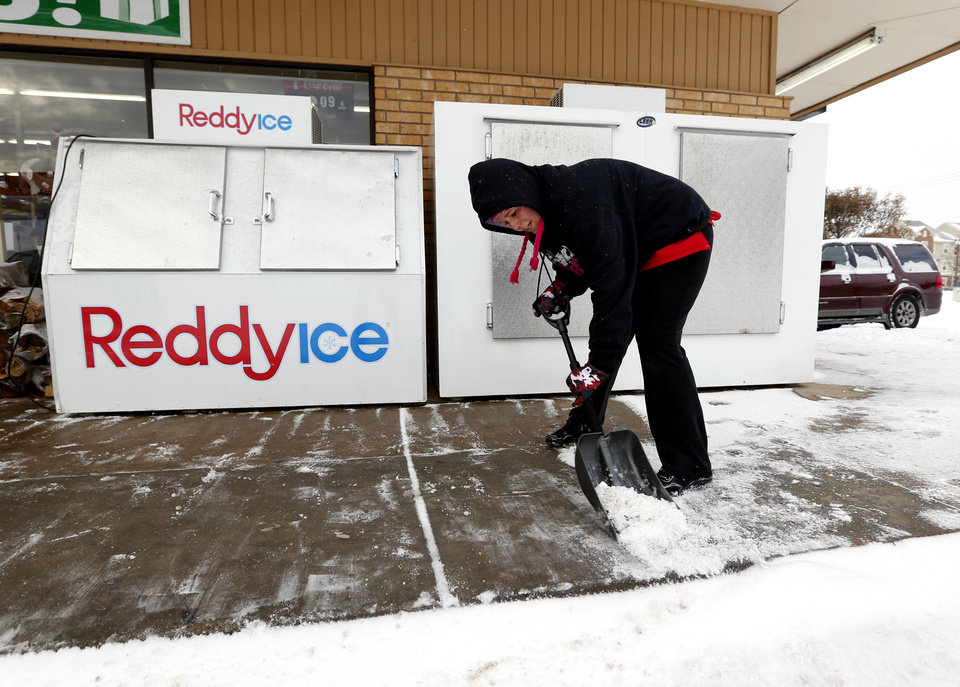 Seven Eleven employee Kayla Kirlin shovels snow from sidewalks after a winter storm on Friday, Dec. 6, 2013 in Norman, Okla.  Photo by Steve Sisney, The Oklahoman