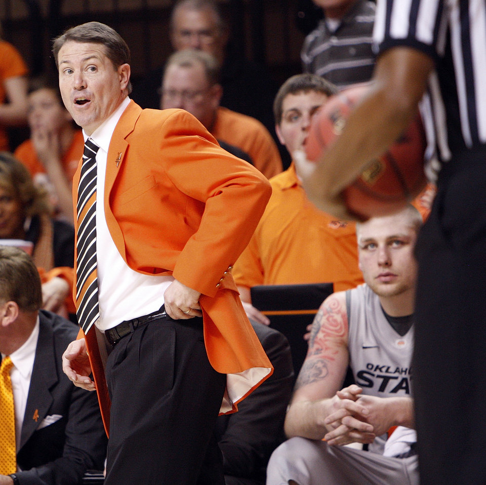 Photo - OSU head coach Travis Ford talks to an official during the Bedlam men's college basketball game between the Oklahoma State University Cowboys and the University of Oklahoma Sooners at Gallagher-Iba Arena in Stillwater, Okla., Monday, Jan. 9, 2012. Photo by Nate Billings, The Oklahoman