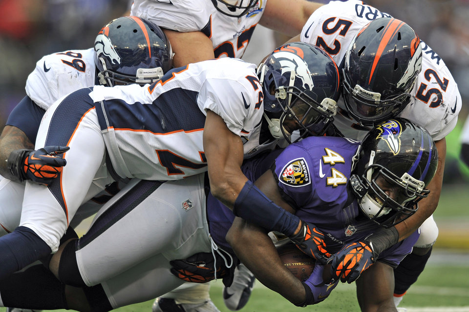 Photo - Baltimore Ravens fullback Vonta Leach is crushed by Denver Broncos defensive tackle Kevin Vickerson (99), cornerback Champ Bailey (24) and outside linebacker Wesley Woodyard (52) during the first half of an NFL football game in Baltimore, Sunday, Dec. 16, 2012. (AP Photo/Gail Burton)