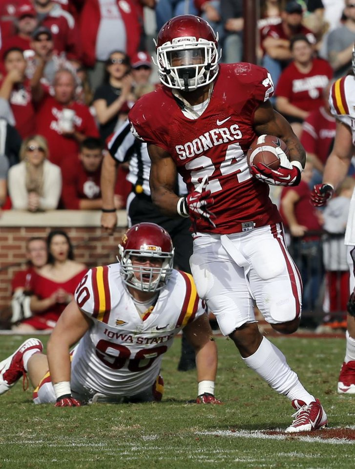 Photo - Oklahoma Sooner's Brennan Clay (24) takes off on a long run for a touchdown during the second half of the college football game between the University of Oklahoma Sooners (OU) and the Iowa State University Cyclones (ISU) at Gaylord Family-Oklahoma Memorial Stadium in Norman, Okla. on Saturday, Nov. 16, 2013. Photo by Steve Sisney, The Oklahoman