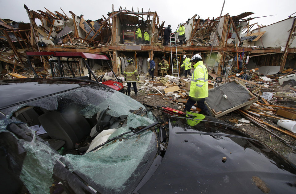 Photo - A smashed car sits in front of an apartment complex destroyed by an explosion at a fertilizer plant in West, Texas, as firefighters conduct a search and rescue Thursday, April 18, 2013. A massive explosion at the West Fertilizer Co. Wednesday night killed as many as 15 people and injured more than 160, officials said overnight. (AP Photo/LM Otero)