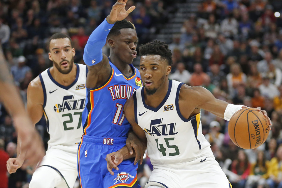 Photo - Oklahoma City Thunder guard Dennis Schroeder, center, guards Utah Jazz guard Donovan Mitchell (45) during the second half of an NBA basketball game Wednesday, Oct. 23, 2019, in Salt Lake City. (AP Photo/Rick Bowmer)