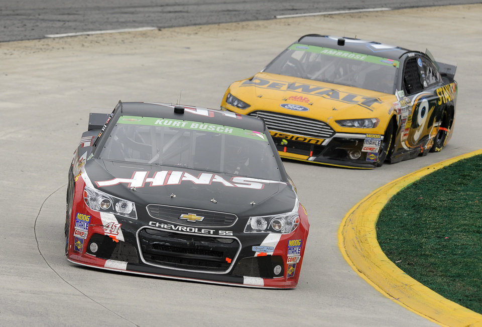 Photo - Driver Kurt Busch (41) drives through turn four as Marcos Ambrose (9) follows during a NASCAR Sprint Cup auto race at Martinsville, Speedway in Martinsville, VA., Sunday March 30, 2014. (AP Photo/Mike McCarn)