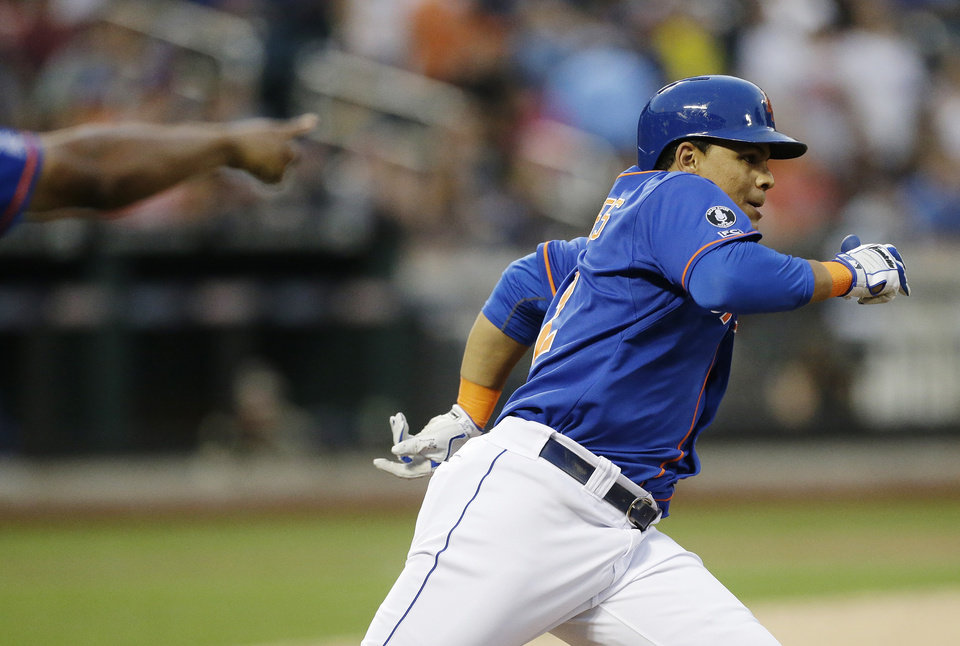 Photo - New York Mets' Juan Lagares runs to second base on a ground-rule double during the second inning of a baseball game against the Chicago Cubs, Saturday, Aug. 16, 2014, in New York. A run scored on the play. (AP Photo/Frank Franklin II)
