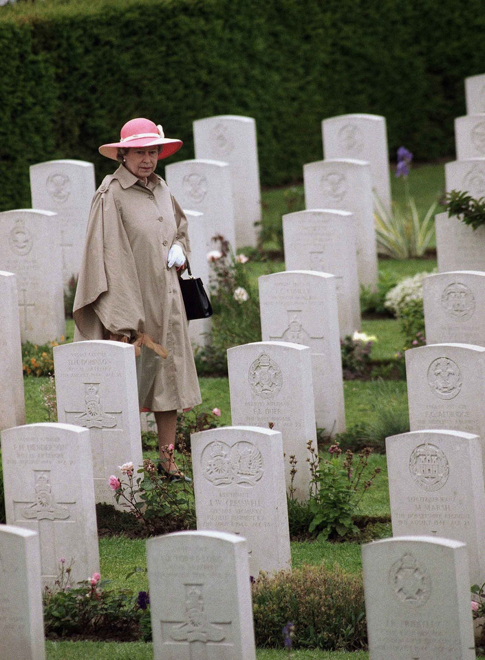 Photo - FILE - In this Monday, June 6, 1994 file photo, Queen Elizabeth II is seen walking through the British Military Cemetery in Bayeux, France, during ceremonies honoring veterans and war dead on the 50th anniversary of D-Day. Queen Elizabeth II and her husband Prince Philip have for the most part stopped traveling overseas _ a reluctant concession to their advancing years _ but they are scrapping this policy next week for the 70th commemoration of the momentous D-Day invasion on June 6, 2014. The perils of World War II directly shaped the lives of Elizabeth, 88, and Philip, 92. The anniversary is so heartfelt that the royal couple is preparing to cross the English Channel once more, this time on a Eurostar train through the Channel Tunnel Elizabeth helped 20 years ago.  (AP Photo/Laurent Rebours, File)