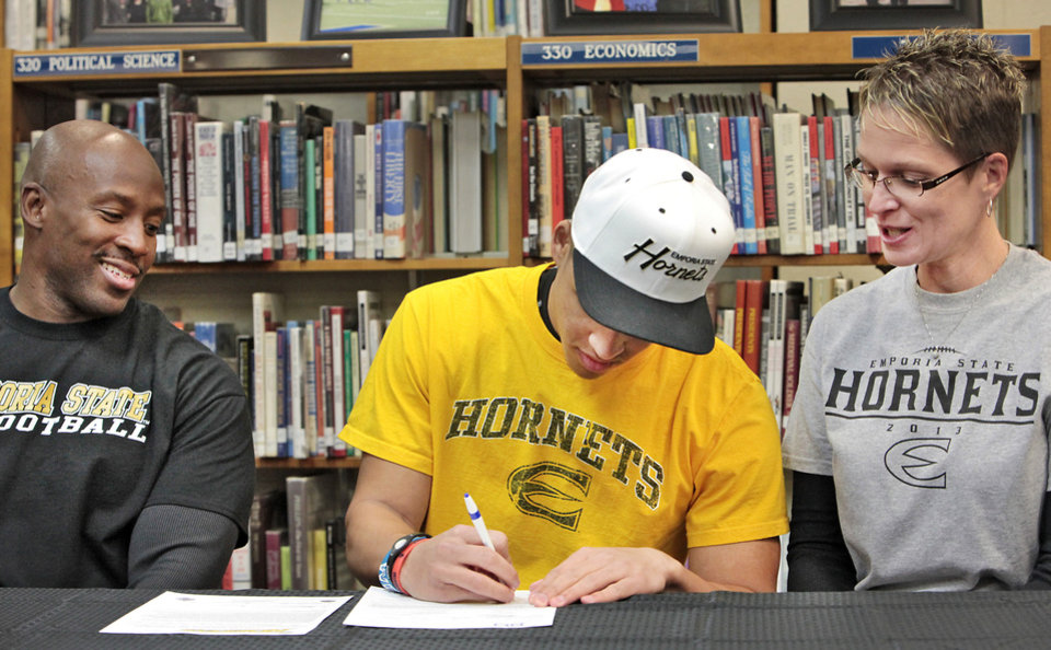 Photo - Football player Kai Callins, center, signs his letter of intent to play for Emporia State at Guthrie High School with his parents Reggie and Cristy, Wednesday, February 4, 2014. Photo by David McDaniel, The Oklahoman