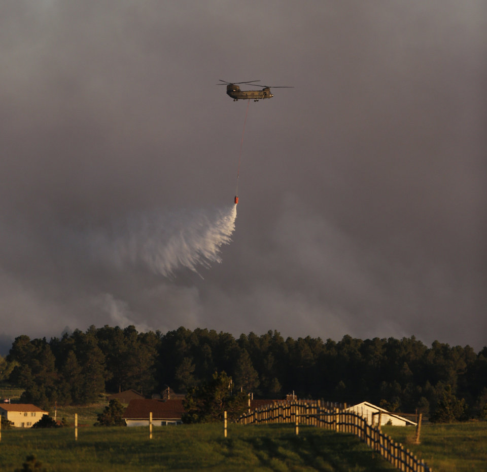 Photo - A U.S. Army helicopter drops a load of water on a wildfire in the Black Forest area north of Colorado Springs, Colo., on Tuesday, June 11, 2013. At least four major wildfires broke out along the front of the Rocky Mountains in Colorado Tuesday, burning a handful of houses and chasing people from thousands of homes in hot, gusty weather. (AP Photo/Ed Andrieski)