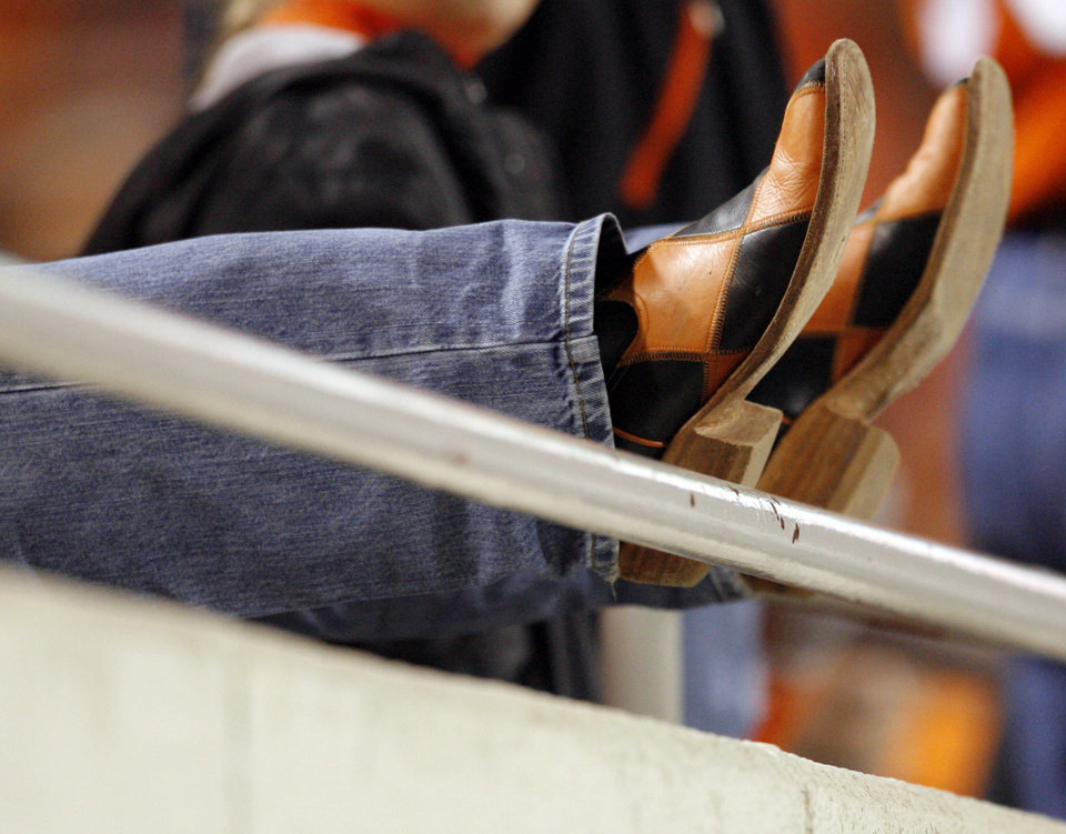 Photo - A Cowboy fan's boots during the college football game between Oklahoma State University (OSU) and the University of Colorado (CU) at Boone Pickens Stadium in Stillwater, Okla., Thursday, Nov. 19, 2009. OSU won, 31-28. Photo by Nate Billings, The Oklahoman