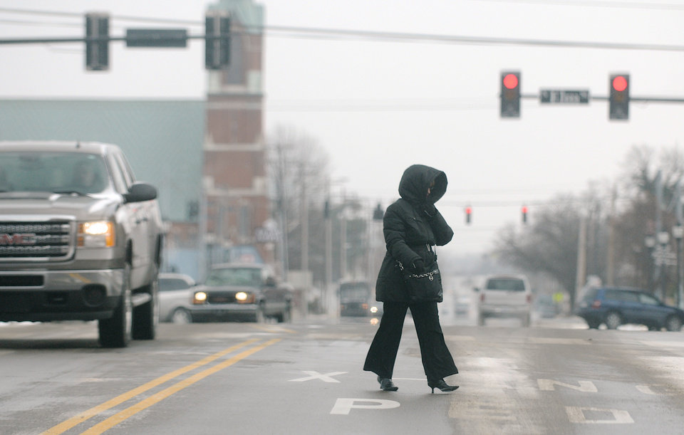 Photo - A pedestrian crosses 2nd Street in downtown Henderson, Ky on a frigid Monday afternoon, Jan. 6, 2014. Temperatures were not forecasted to get above 3 degrees with lows dipping to -2 tonight. (AP Photo/The Gleaner, Darrin Phegley)