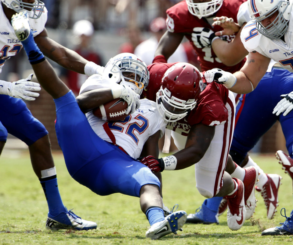 Oklahoma's Jordan Phillips (80) stops Tulsa's Trey Watts (22) during the second half of a college football game between the University of Oklahoma Sooners (OU) and the Tulsa Golden Hurricane (TU) at Gaylord Family-Oklahoma Memorial Stadium in Norman, Okla., on Saturday, Sept. 14, 2013. Phillips was shaken up on the play.  Photo by Steve Sisney, The Oklahoman