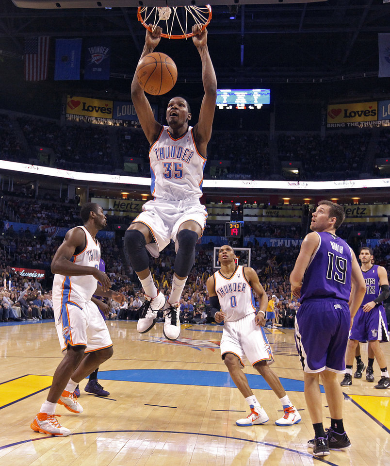 Photo - The Thunder's Kevin Durant (35) dunks the ball over the Kings' Beno Udrih (19) during the NBA basketball game between the Oklahoma City Thunder and The Sacramento Kings on Tuesday, Feb. 15, 2011, Oklahoma City Okla.  Photo by Chris Landsberger, The Oklahoman