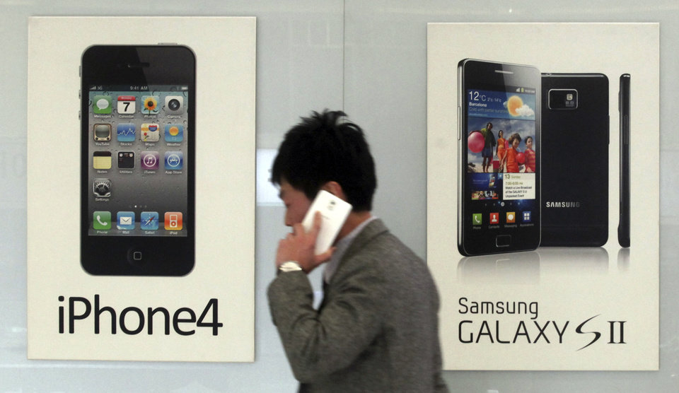 Photo - FILE - In this Nov. 22, 2013 file photo, a man walks past banners advertising smartphones by Samsung and Apple at a mobile phone shop in Seoul, South Korea. The high-stakes battle between the world's largest smartphone makers is scheduled to wrap up this week after a monthlong trial that has pulled the curtain back on just how very cutthroat the competition is between Apple and Samsung. Closing arguments in the patent-infringement case are scheduled to begin Monday, April 28, 2014 with the two tech giants accusing each other, once again, of ripping off designs and features. At stake: $2 billion if Samsung loses, a few hundred million if Apple loses. (AP Photo/Yonhap, Han Sang-kyun, File)  KOREA OUT