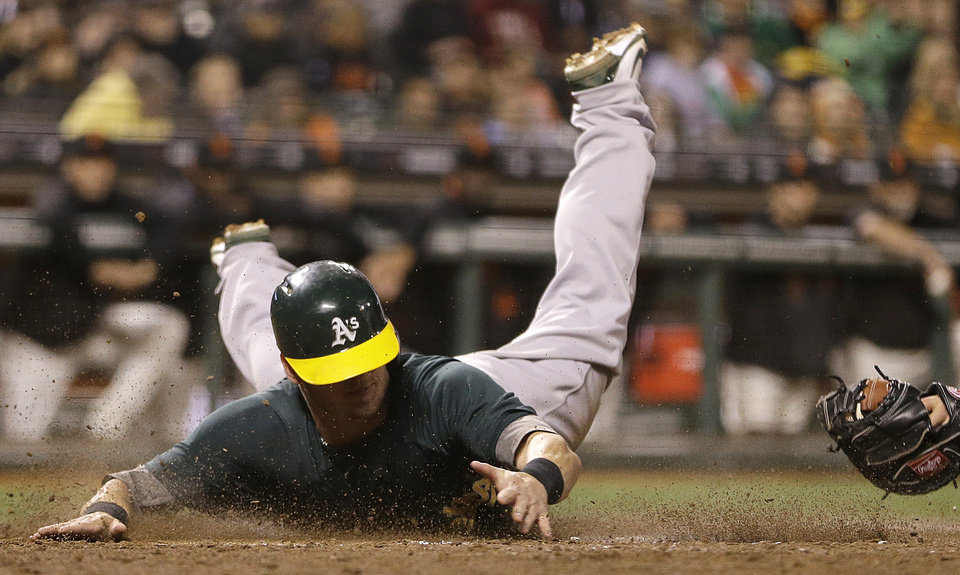 Oakland Athletics' Josh Donaldson slides to score against the San Francisco Giants in the sixth inning of an exhibition baseball game Thursday, March 28, 2013, in San Francisco. Donaldson scored on a bunt by Eric Sogard. (AP Photo/Ben Margot)