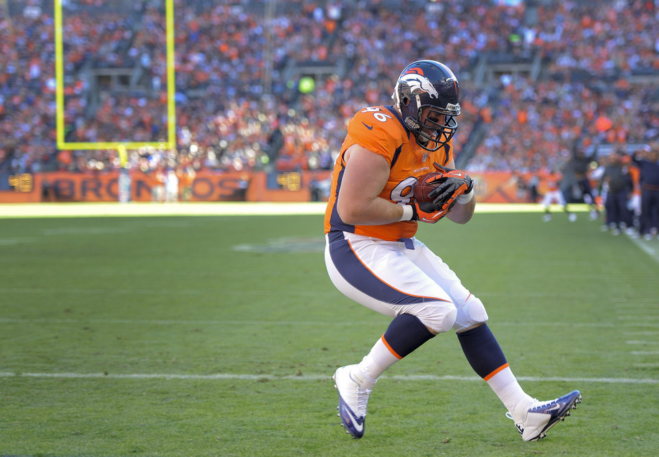 Photo - Denver Broncos defensive tackle Mitch Unrein (96) catches a pass for a touchdown against the Tampa Bay Buccaneers in the first quarter of an NFL football game, Sunday, Dec. 2, 2012, in Denver. (AP Photo/Jack Dempsey)
