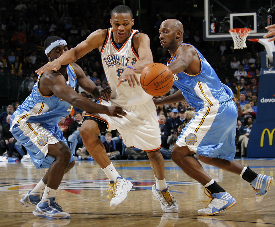 Photo - Oklahoma City's Russell Westbrook (0) tries to slip between the defense of Denver's Ty Lawson (3) , left, and Chauncey Billups (1) during the NBA basketball game between the Oklahoma City Thunder and the Denver Nuggets at the Ford Center in Oklahoma City, Friday, January 29, 2010. Oklahoma City won, 101-84. Photo by Nate Billings, The Oklahoman ORG XMIT: KOD