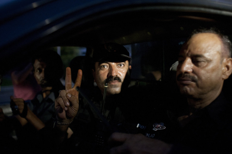 Photo - A Pakistani commando gestures while leaving the Jinnah International Airport in Karachi where security forces continue to battle militants Monday, June 9, 2014 in Pakistan. Gunmen disguised as police guards attacked a terminal at Pakistan's busiest airport with machine guns and a rocket launcher during a five-hour siege that killed over a dozen people as explosions echoed into the night, while security forces retaliated and killed all the attackers, officials said Monday. (AP Photo/Shakil Adil)