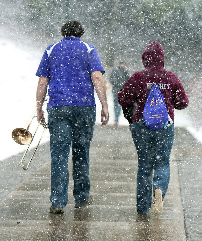 Junior Aaron Raffeinner, 20, left, and Holly Doherty, 19, a sophomore, members of the James Madison University Pep Band, leave the Convocation Center as the snow falls after performing during the second round Women's National Invitational Tournament basketball game with North Carolina State Sunday March 24, 2013 in Harrisonburg, Va. (AP Photo/Daily News-Record, Michael Reilly)