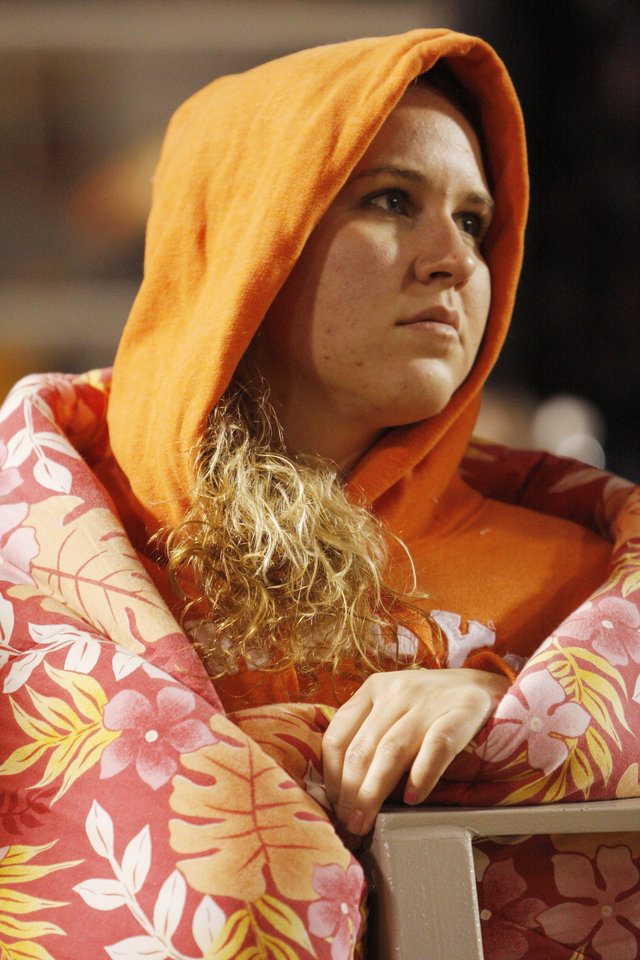 Photo - Kira Tyson, a student from Ridgecrest Calif., tries to stay warm during the college football game between the Oklahoma State University Cowboys (OSU) and the University of Texas Longhorns (UT) at Boone Pickens Stadium in Stillwater, Okla., Saturday, Oct. 31, 2009. Photo by Doug Hoke, The Oklahoman