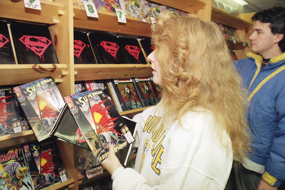 "Lori Horne of Boston grabs several copies of tthe ""Death of Superman"" comic book from the shelves of Comicopia in Boston during the first hours of sales Wednesday, Nov. 18, 1992. Chris Viveiros of Boston holds his copy of the comic book in the background. Another local store sold its entire supply of copies before noon. (AP Photo/Lisa Bull) <strong>Lisa Bull</strong>"