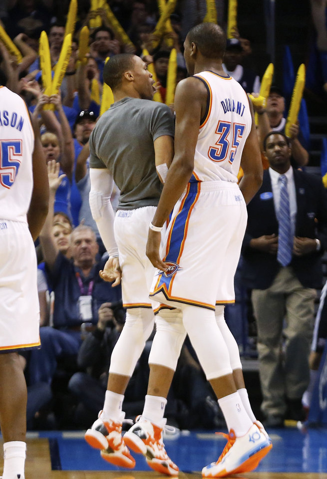 Photo - Oklahoma City Thunder guard Russell Westbrook (0) chest-bumps teammate Kevin Durant (35) during a timeout in the fourth quarter of an NBA basketball game against the Houston Rockets in Oklahoma City, Tuesday, March 11, 2014. Oklahoma City won 106-98. (AP Photo/Sue Ogrocki)