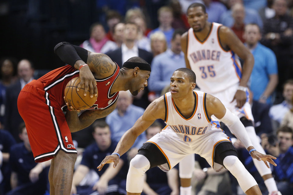 Photo - Miami Heat forward LeBron James, left, keeps the ball from Oklahoma City Thunder guard Russell Westbrook (0) in the fourth quarter of an NBA basketball game in Oklahoma City, Thursday, Feb. 14, 2013. Thunder forward Kevin Durant (35) watches at rear. Miami won 110-100. (AP Photo/Sue Ogrocki) ORG XMIT: OKSO114