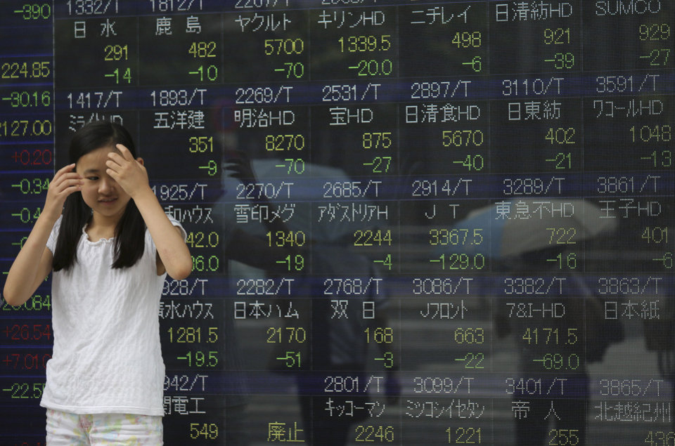 Photo - A girl takes shelter from the rain by an electronic stock board of a securities firm in Tokyo Friday, Aug. 8, 2014. Asian stocks sank Friday as jitters over the crises in Iraq and Ukraine escalated but Chinese stocks rose after trade figures showed surprisingly strong growth in exports. In Japan, the 225-issue Nikkei Stock Average dived 454.00 points, or 2.98 percent, and finished at 14,778.37, hitting a two-month low. (AP Photo/Eugene Hoshiko)