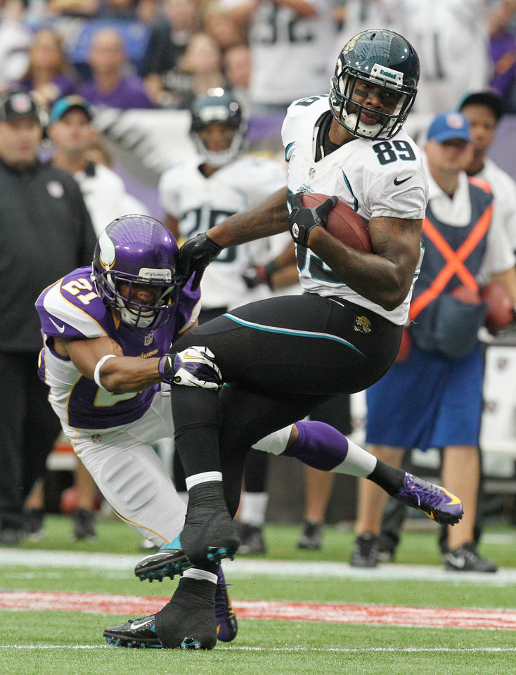 Photo -   Jacksonville Jaguars tight end Marcedes Lewis (89) tries to break a tackle by Minnesota Vikings cornerback Josh Robinson, left, during the first half of an NFL football game on Sunday, Sept. 9, 2012, in Minneapolis. (AP Photo/Genevieve Ross)