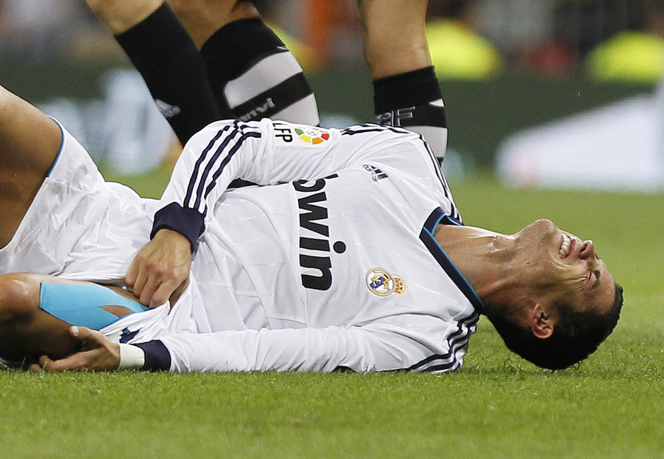 Photo -   Real Madrid's Cristiano Ronaldo from Portugal reacts after receiving an injury during a Spanish La Liga soccer match against Granada at the Santiago Bernabeu stadium in Madrid, Spain, Sunday, Sept. 2, 2012. (AP Photo/Andres Kudacki)