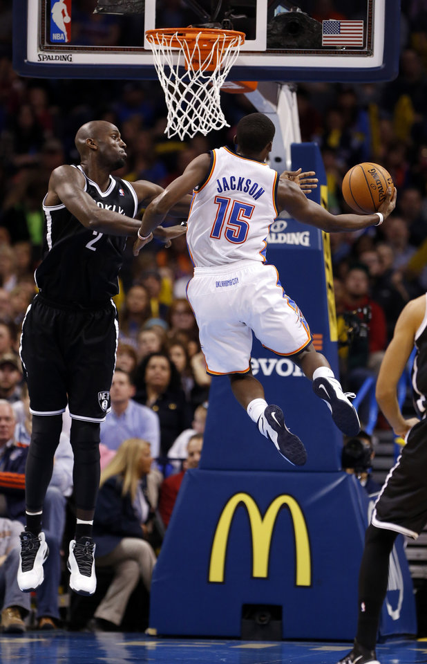 Photo - Thunder's Reggie Jackson (15) drives to the basket past Brooklyn's Kevin Garnett in the second half of an NBA basketball game where the Oklahoma City Thunder were defeated 95-93 by the Brooklyn Nets at the Chesapeake Energy Arena in Oklahoma City, on Thursday, Jan. 2, 2014. Photo by Steve Sisney, The Oklahoman
