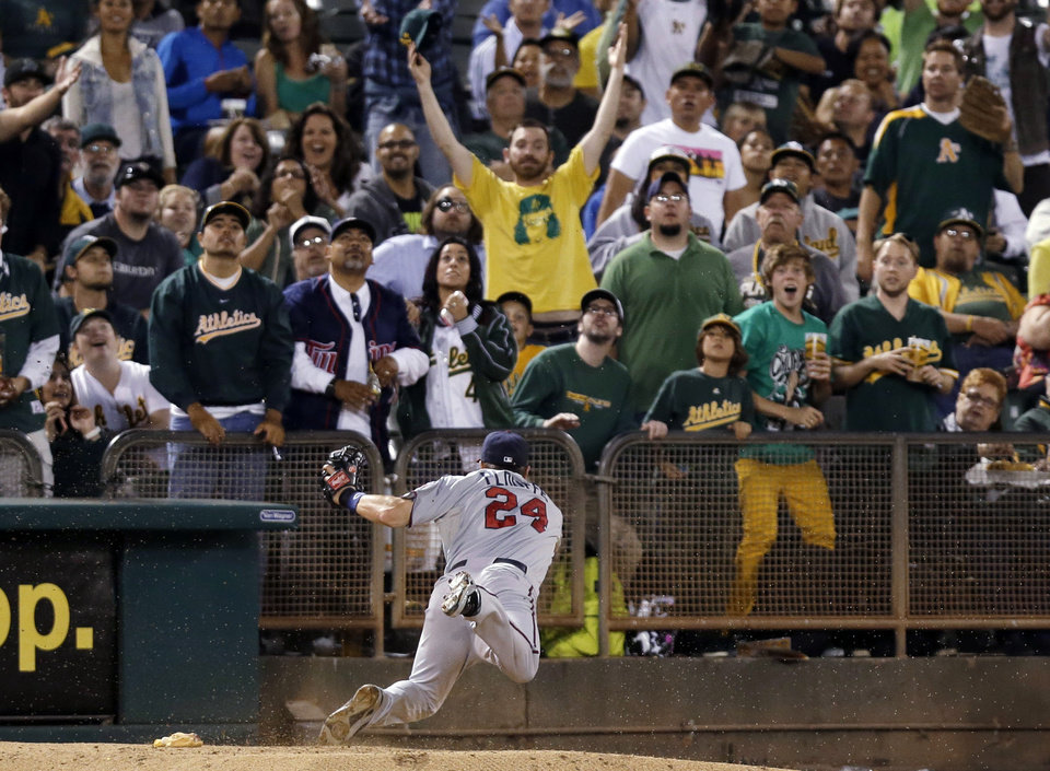 Minnesota Twins third baseman Trevor Plouffe falls down over the bullpen mound chasing a foul ball by Oakland Athletics' Daric Barton during the second inning of a baseball game Thursday, Sept. 19, 2013, in Oakland, Calif. (AP Photo/Marcio Jose Sanchez)