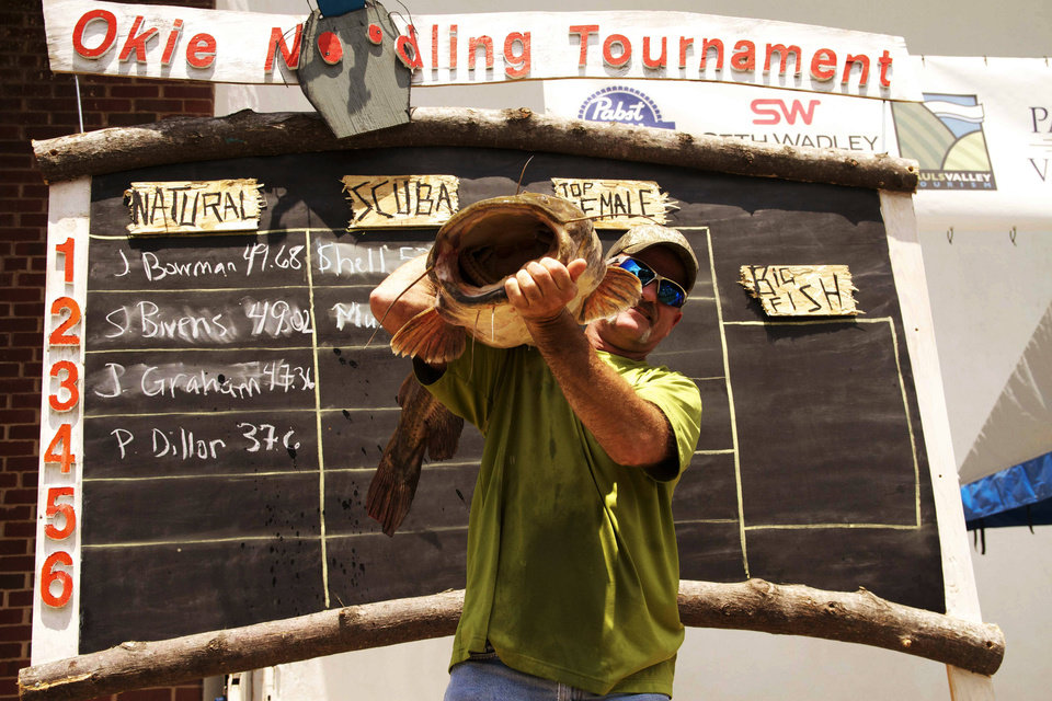 Photo - Scooter Bivins of Temple, one of the cast members of the cable television show Mudcats, holds up a flathead at the Okie Noodling Tournament in Pauls Valley.  Photo provided