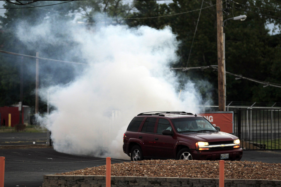 Photo - A car pulls away as tear gas is deployed by police Monday, Aug. 11, 2014, in Ferguson, Mo. The FBI opened an investigation Monday into the death of 18-year-old Michael Brown, who police said was shot multiple times Saturday after being confronted by an officer in Ferguson. Authorities in Ferguson used tear gas and rubber bullets to try to disperse a large crowd Monday night that had gathered at the site of a burned-out convenience store damaged a night earlier, when many businesses in the area were looted. (AP Photo/Jeff Roberson)