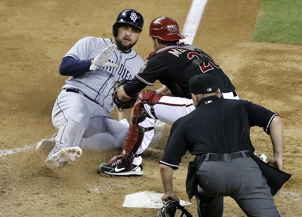 Photo - Arizona Diamondbacks catcher Miguel Montero, right, tags out San Diego Padres' Yonder Alonso at the plate during the fifth inning of a baseball game, Saturday, May 25, 2013, in Phoenix. (AP Photo/Matt York)