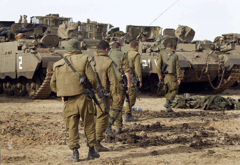 Israeli soldiers with armored vehicles gather in a staging ground near the border with Gaza Strip, southern Israel, Friday, Nov. 16, 2012. Fierce clashes between Israeli forces and Gaza militants are continuing for the third day.(AP Photo/Tsafrir Abayov) ORG XMIT: JRL150
