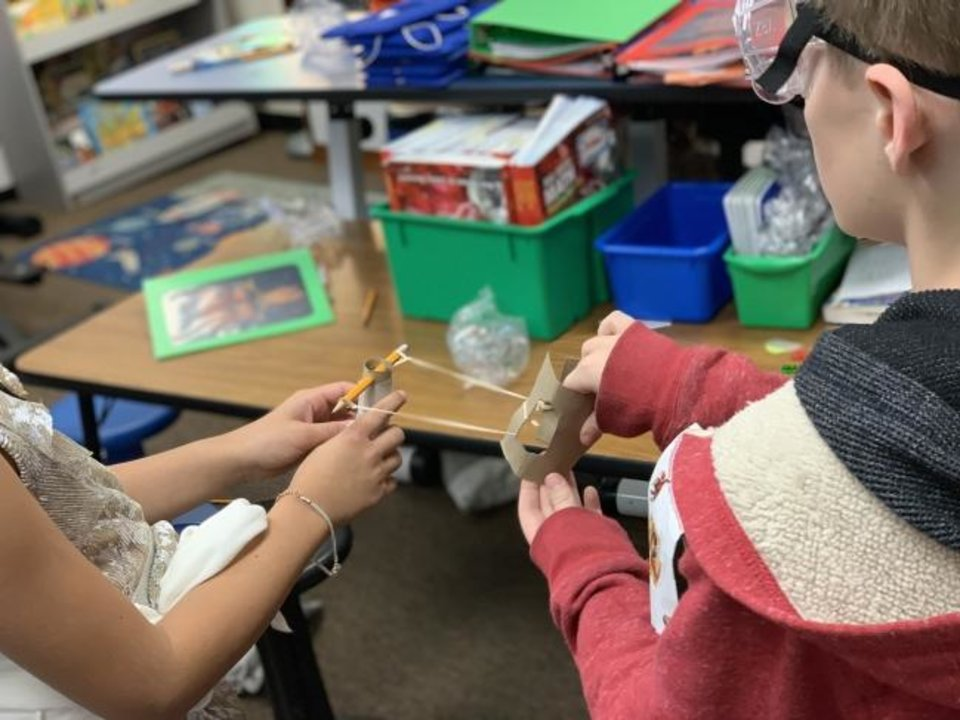 Photo -  Fourth-grade students at Coronado Heights Elementary build a slingshot with instructions from the Devon Thunder Explorers Program, which encourages STEM activities in schools. The students' teacher, Dawn Dilley, won $500 for her classroom by having her students participate in the program. [Photo provided]