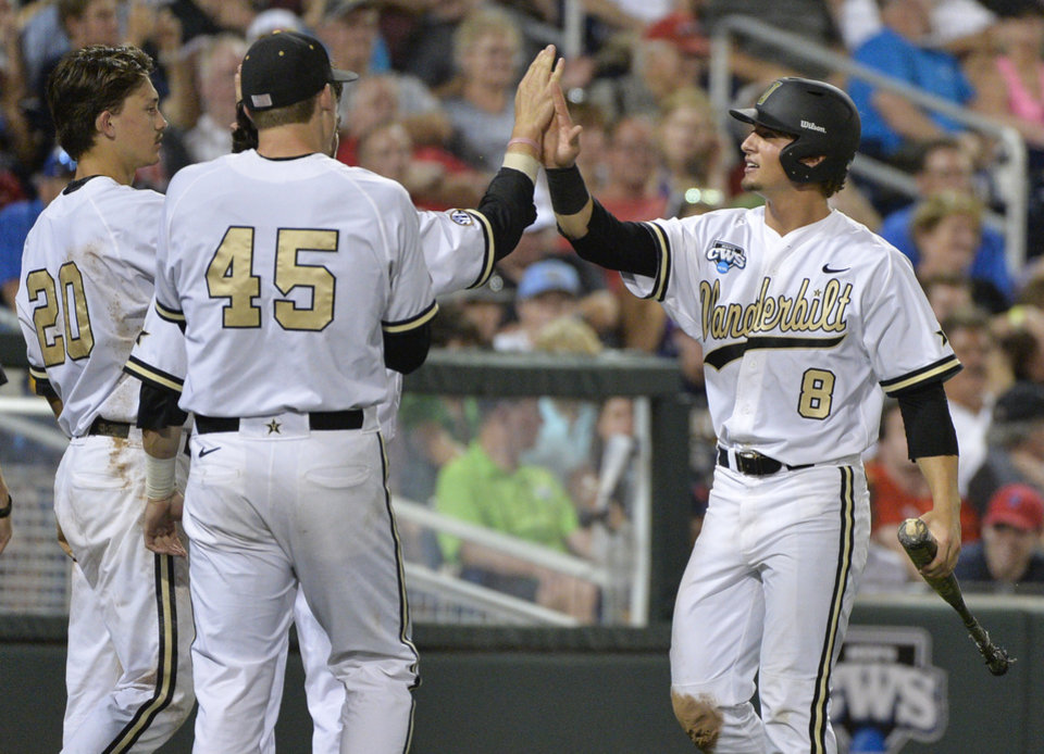 Photo - Vanderbilt's Rhett Wiseman (8) is greeted by Tyler Ferguson (45) and Bryan Reynolds (20) after he scored a run against UC Irvine on a single by John Norwood in the seventh inning of an NCAA baseball College World Series game in Omaha, Neb., Monday, June 16, 2014. (AP Photo/Ted Kirk)