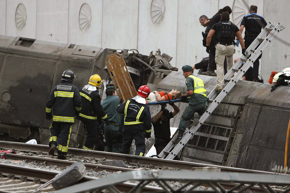 Photo - A woman is evacuated by emergency personnel at the scene of a train derailment in Santiago de Compostela, Spain, on Wednesday, July 24, 2013. A train derailed in northwestern Spain on Wednesday night, toppling passenger cars on their sides and leaving at least one torn open as smoke rose into the air. Dozens were feared dead, with possibly even more injured. (AP Photo/ El correo Gallego/Antonio Hernandez)