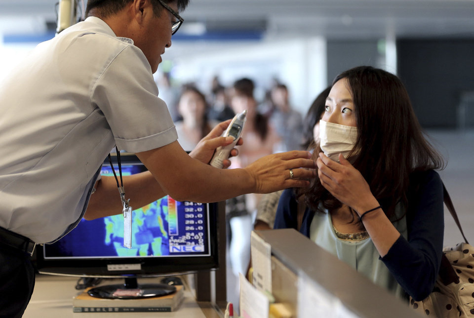 Photo - A South Korean quarantine officer, left, checks body temperature of a passenger against possible infections of Ebola virus at the Incheon International Airport in Incheon, South Korea, Friday, Aug. 8, 2014. South Korea has been stepping up monitoring of its citizens returning from trips to West Africa and other areas affected by the deadly Ebola virus. (AP Photo/Yonhap, Choe Jae-koo)  KOREA OUT