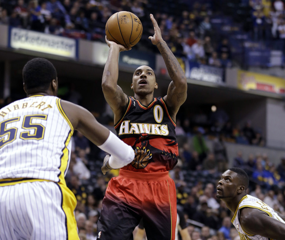 Atlanta Hawks guard Jeff Teague shoots between Indiana Pacers center Roy Hibbert, left, and guard Lance Stephenson in the first half of an NBA basketball game in Indianapolis, Tuesday, Feb. 5, 2013. (AP Photo/Michael Conroy)