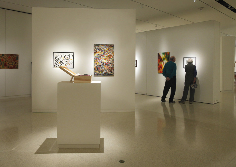 Photo - Visitors to the Fred Jones Jr. Museum of Art look at students' art works at a previous year's student exhibition. Students will celebrate 100 years of annual art shows in January. OKLAHOMAN ARCHIVES  STEVE SISNEY